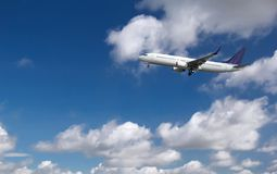 Commercial passenger airplane landing or taking off from the airport with blue cloudy sky in the background royalty free stock photo