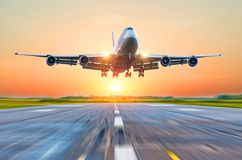 Passenger aircraft landing on the runway at the airport at sunset clear sky. Stock Photo