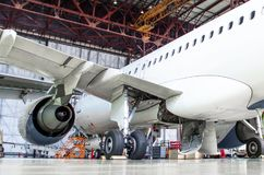 Passenger aircraft on maintenance of engine and fuselage repair in airport hangar. Rear view, under the wing. Stock Images