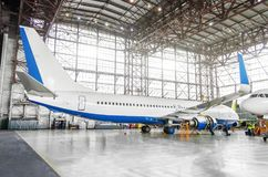Passenger aircraft on maintenance of engine and fuselage repair in airport hangar. View airplane completely from behind to tail. Passenger aircraft on Royalty Free Stock Photos
