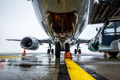 Passenger aircraft on maintenance and flight preparation. View under airplane fuselage in airport stock image
