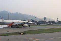 Passenger aircraft on the runway of Hong Kong. A Passenger aircraft on the runway of Hong Kong International Airport site stock photo
