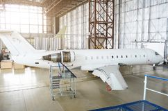 Passenger aircraft, side view - on maintenance of engine on tail and fuselage repair in airport hangar. Passenger aircraft, side view - on maintenance of engine stock image
