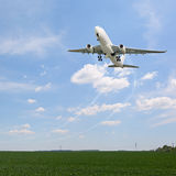 Passenger aircraft taking off. Over the fields Stock Image