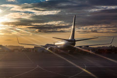 Passenger airliner riding on runway in sunset lights. Passenger aircraft riding on runway in sunset lights Royalty Free Stock Photos