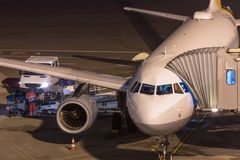 Passenger airplane at an aiport gate at night. A passenger airplane at an aiport gate at night Stock Photo