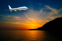 Passenger airplane in the clouds at sunset Royalty Free Stock Photo