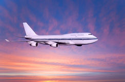 Passenger airplane in the clouds at sunset or dawn. Stock Image