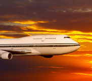 Passenger airplane in the clouds at sunset or dawn. Royalty Free Stock Images