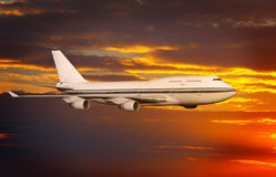 Passenger airplane in the clouds at sunset or dawn. Royalty Free Stock Photos