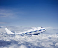 Passenger airplane in the clouds. Stock Image