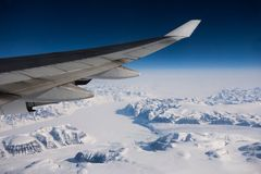 The passenger airplane flies over Greenland. Wing, blue sky, ice. Travel around World royalty free stock photography