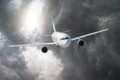 Passenger airplane flies through the turbulence zone through the lightning of storm clouds in bad weather. royalty free stock photos