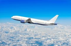 Passenger airplane fly on a hight above overcast clouds and blue sky. stock images