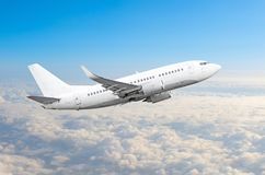 Passenger airplane fly on a hight above overcast clouds and blue sky. stock photo