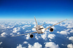 Passenger airplane flying above clouds Stock Images