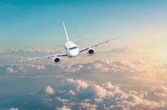 Passenger airplane flying above overcast clouds green pink gradient sky stock photo
