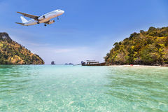 Passenger airplane flying above small island in tropical andaman sea Stock Images