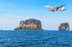 Passenger airplane flying above small island in tropical andaman sea. Royalty Free Stock Images