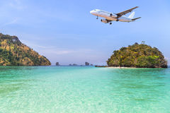 Passenger airplane flying above small island in tropical andaman sea. Stock Photo
