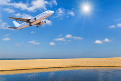 Passenger airplane flying above tropical beach with sunlight Stock Photo