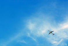 Passenger airplane flying in blue sky. Aircraft flying on the blue sky with clouds. Concept: travel by air transport Royalty Free Stock Images
