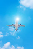 Passenger airplane flying in the blue sky with sunshine Royalty Free Stock Image