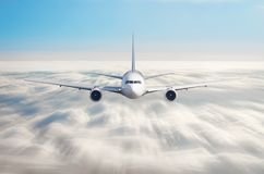 Passenger airplane flying at flight level high in the sky above overcast clouds and blue sky. View directly in front, exactly. Royalty Free Stock Photography