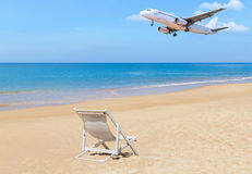 Passenger airplane flying landing above tropical beach with white wooden beach chair Royalty Free Stock Images