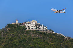 Passenger airplane flying over above Wat Khao Chong Krachok buddhist temple on mountain in Thailand Royalty Free Stock Photography