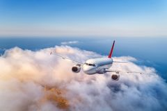 Passenger airplane flying over clouds at sunset stock images