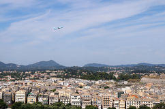 Passenger airplane flying over Corfu town Royalty Free Stock Image