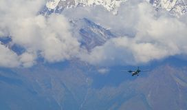 A passenger airplane flying over the mountains stock photos
