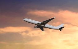 Passenger airplane flying during sunset royalty free stock images