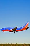Passenger Airplane Landing - 2. Vertical view of a colorful Boeing 737 passenger airliner with wheels down about to land at a major airport. Clear and open space Stock Images