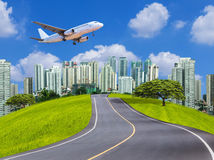 Passenger airplane landing above modern city with asphalt road Royalty Free Stock Photography