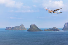Passenger airplane landing above small island in blue sea Stock Photos