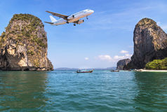 Passenger airplane landing above small island in blue sea and tropical beach Stock Photography