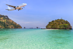 Passenger airplane landing above small island in blue sea and tropical beach Stock Images