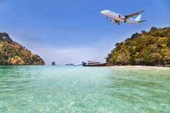 Passenger airplane landing above small island in blue sea and tropical beach Royalty Free Stock Images