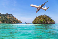 Passenger airplane landing above small island in blue sea and tropical beach Royalty Free Stock Image