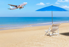 Passenger airplane landing above tropical beach with white wooden beach chair and blue parasol. On blue sky background. travel destinations concept stock images