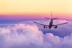 Passenger airplane landing against amazing yellow and pink colorful sky with clouds during sunset. Travel background stock photography