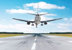 Passenger airplane landing at in good clear weather with a blue sky clouds on a runway. Back view. Stock Image