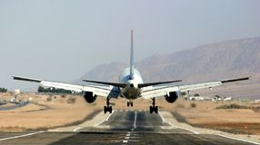 Passenger airplane landing on runway. Stock Photo