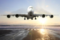 Passenger airplane landing on runway in airport. Evening Stock Photography