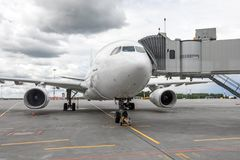Passenger airplane in the parking at the airport with a nose forward and a gangway royalty free stock image