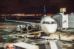 Passenger airplane on runway near the terminal in an airport at night time. Airport land crew doing flight service for passenger a. Irplane at night time Stock Photo