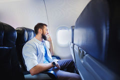 Passenger of airplane talking on mobile phone Stock Image