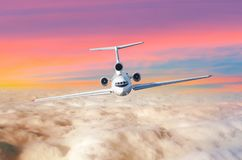 Passenger airplane with three engines on the tail flying above the clouds horizon sky with bright sunset colors., the view is exac Stock Photography